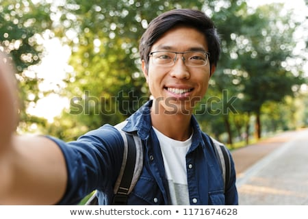 Pleased asian male student in eyeglasses making selfie Stock photo © deandrobot