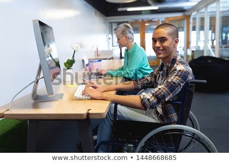Side view of young disabled mixed-race female executive using laptop while talking on mobile phone a Stock photo © wavebreak_media
