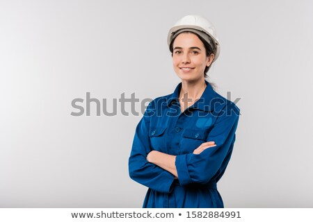 Happy young cross-armed female engineer in blue workwear and hardhat Stock photo © pressmaster