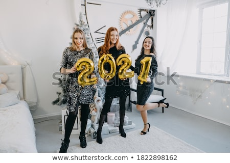three beautiful smiling women in shiny dresses stock photo © deandrobot