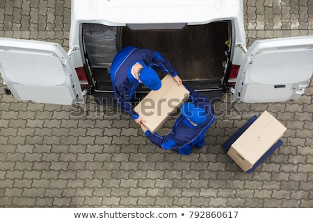 male mover unloading the cardboard boxes from truck stock photo © andreypopov