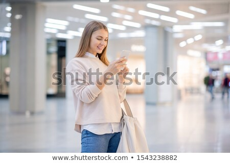 Pretty casual woman scrolling in smartphone while searching for online goods Stock photo © pressmaster