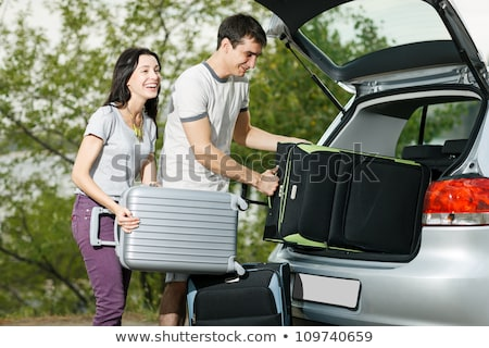 Woman loads suitcase into car boot or trunk Stock photo © Kzenon