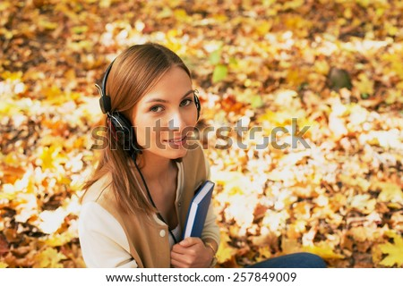 Student sitting with headphones among maple leaves Stock photo © Agatalina