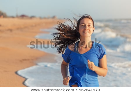 Cheerful fit woman running from sea Stock photo © dash