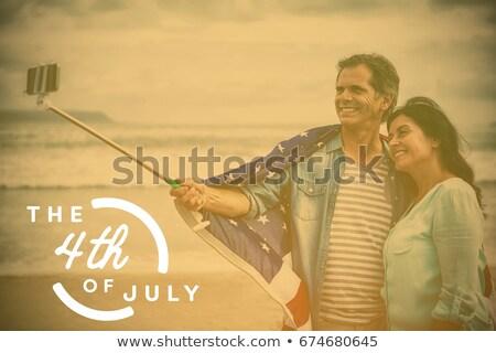 couple wrapped in american flag taking selfie on beach stock photo © wavebreak_media