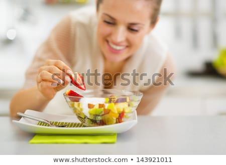 Jonge huisvrouw eten vers fruit salade keuken Stockfoto © dashapetrenko