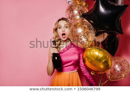 Playful young blonde with bottle. Isolated stock photo © acidgrey