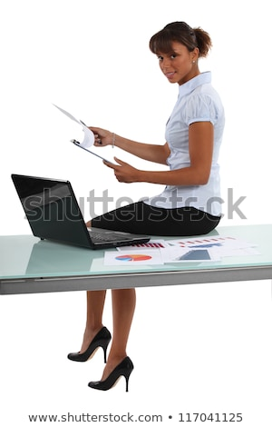 Businesswoman perched on a desk with statistics Stock photo © photography33