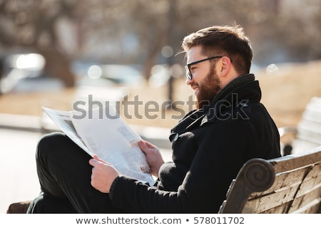 man reading newspaper in the city park stock photo © bluering