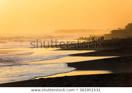 sunset on the kuta beach with reflection in the water on the island of bali stock photo © galitskaya