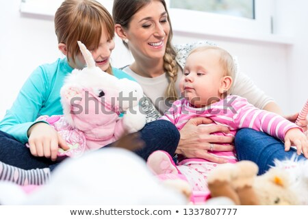 Mother playing with baby and bigger daughter Stock photo © Kzenon