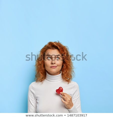 Vertical image of thoughtful young woman wears white jumper and black trousers, holds takeaway coffe Stock photo © vkstudio