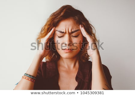 Young asian woman with closed eyes touching her head Stock photo © deandrobot