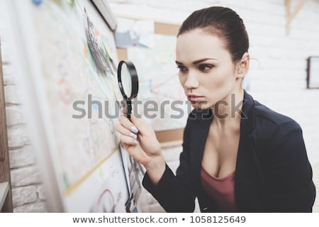 Detective looking for clues with magnifying glass Stock photo © colematt