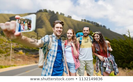 friends with smartphone over hills of big sur Stock photo © dolgachov