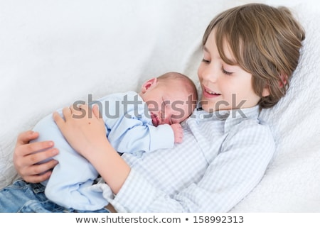 happy laughing boy holding his sleeping newborn baby sister stock photo © lopolo