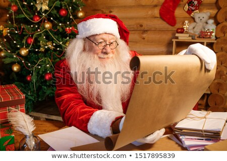 Santa in costume unrolling big paper with Christmas wishes Stock photo © pressmaster