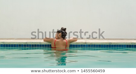 Rear view of beautiful young mixed-race woman standing at beach on a sunny day. She is looking away Stock photo © wavebreak_media