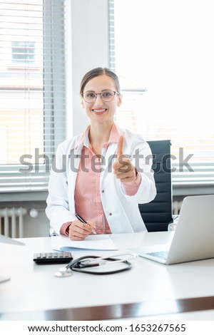 Doctor woman giving thumbs-up sitting on desk in her office Stock photo © Kzenon