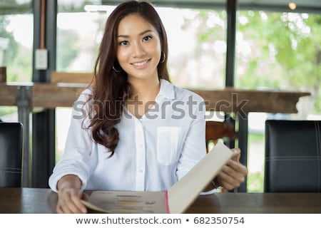 Portrait of the young beautiful smiling woman outdoors eating ic Stock photo © HASLOO