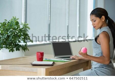 Executive exercising with dumbbells while using laptop Stock photo © wavebreak_media