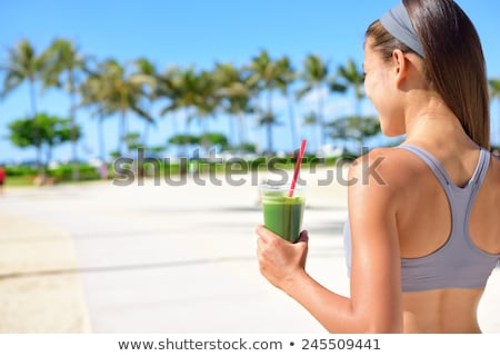 Young beautiful woman drinking vegetable smoothie after fitness at home and smile . Fitness and heal Stock photo © galitskaya