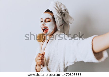 Foto stock: Beautiful young woman relaxing with face mask at home. Happy joyful woman applying black mask on fac