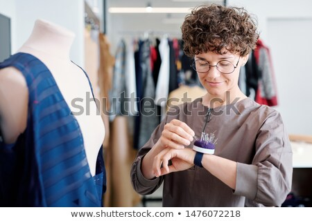 Young tailor taking pin from pincushion on her wrist during work Stock photo © pressmaster