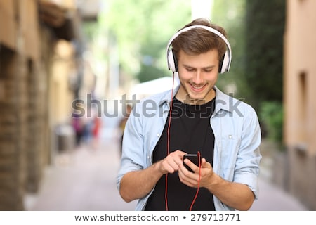 Portrait of happy handsome man using earphones and smiling Stock photo © deandrobot