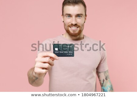 Image of young bearded man wearing basic white t-shirt smiling at camera Stock photo © deandrobot