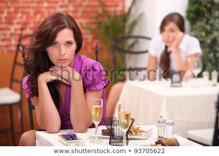 angry woman at the restaurant on the table an unopened gift and flutes of sparkling wine stock photo © photography33