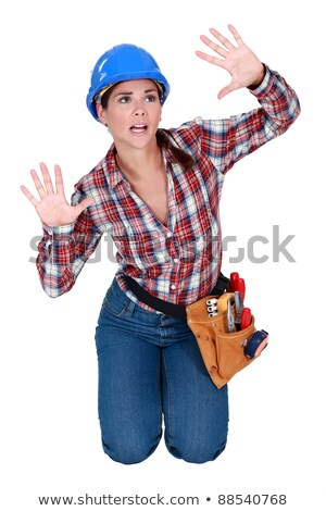 Young woman laborer gesturing, kneeling on white background Stock photo © photography33