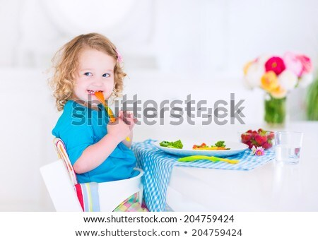 Stock photo: young child eating tomatoes in high chair