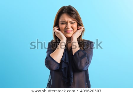 frustrated young woman with fingers in her ears stock photo © williv