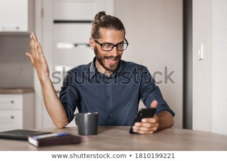 Shocked happy business man using smartphone and rejoices Stock photo © deandrobot