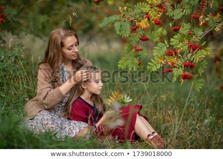 Young mom stroking her saughter's hair Stock photo © konradbak