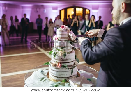 the bride and groom cut a beautiful wedding white cake decorated with berries stock photo © ruslanshramko