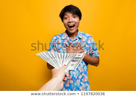 Excited asian man receiving money banknotes Stock photo © deandrobot