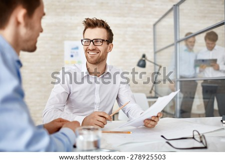 Young businessman with paper consulting with colleague Stock photo © pressmaster