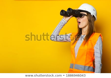 young woman in a yellow work uniform glasses and helmet in industrial environmentoil platform or l stock photo © galitskaya