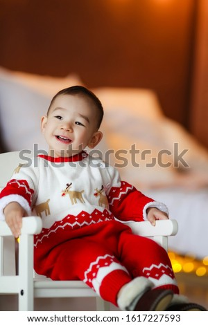 Cheerful boy 2-3 years of Asian appearance in a room at home in a red Christmas suit Stock photo © ElenaBatkova