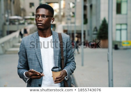 Image of thinking businessman using cellphone and earphones Stock photo © deandrobot
