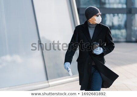 Shot of young man poses outdoor at street, looks aside, wears sunglasses, rubber gloves, medical mas Stock photo © vkstudio