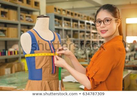 Female designer measuring the length of dress on mannequin Stock photo © wavebreak_media