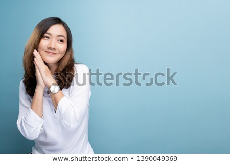 Thinking asian beautiful woman isolated over blue background holding credit card and money. Stock photo © deandrobot