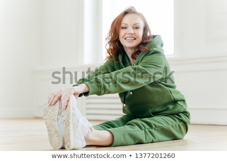 Photo of delighted red haired female stretches legs, has fitness training, wears sportshoes and trac Stock photo © vkstudio