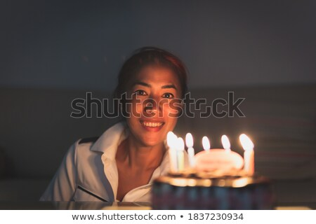 attractive female readies to blow out birthday cake candles stock photo © cboswell