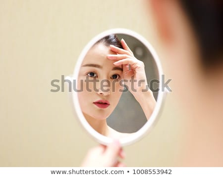 Young woman examining make-up in mirror Stock photo © stokkete