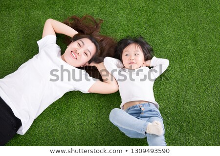 a mother and daughter lying on a lawn stock photo © is2